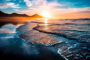 Waves breaking on the shore at sunset.