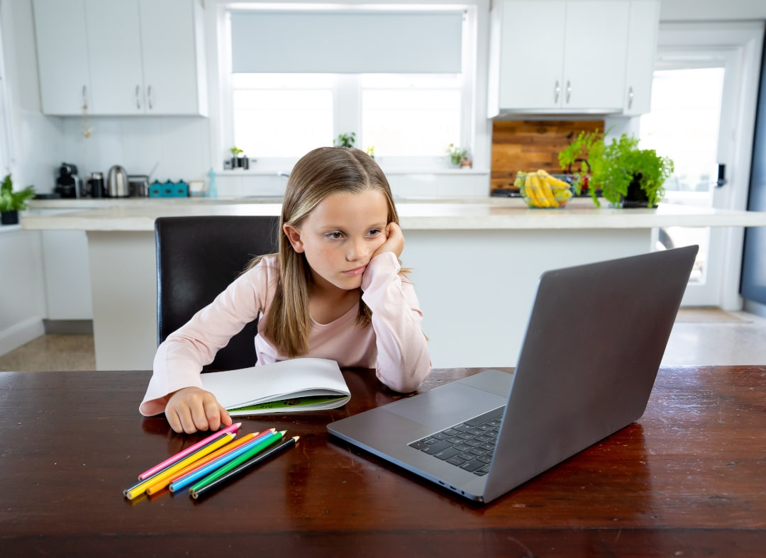 The new normal: a young girl attending school via online meeting software.