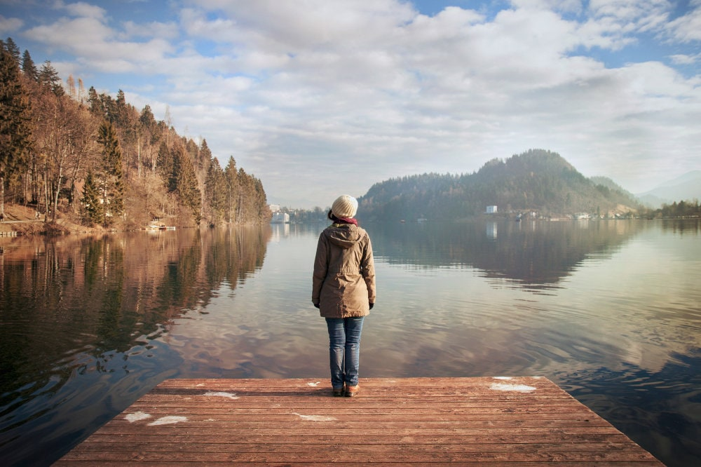 A woman standing on a dock overlooking a lake on a sunny winter day.